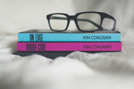 Black reading glasses sit on top of two books. The books are spine side out showing the name Kim Congram as the author, and Rough Code, and On Edge on the top of the spine. On Edge is in electric blue with black font, while Rough Code is in deep pink with Black font.