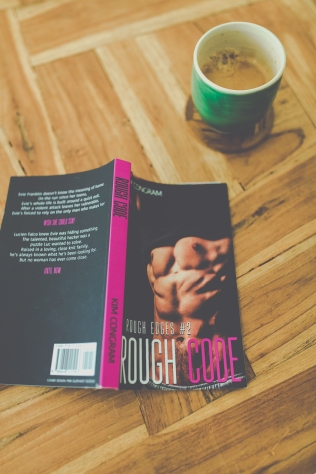 Rough Code paperback placed on wooden floor. A cup of coffee is in the upper right-hand corner of the photo.